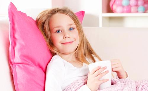 Девочка на розовой подушке не грустит и пьёт травяной чай