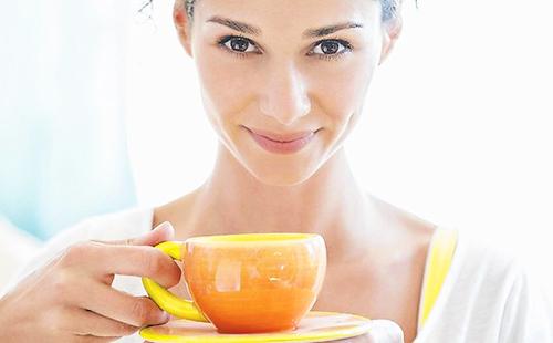 Кареглазая девушка пьёт настой из оранжевой чашки