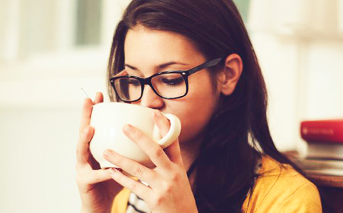 Девушка в очках осторожно отпивает отвар