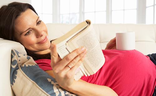 Беременная женщина пьёт травяной чай и читает книжку