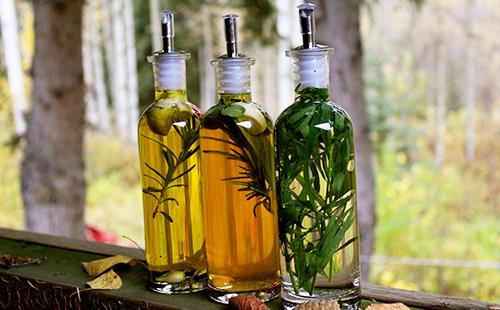 Три бутылки, полные масла и зелёных листьев