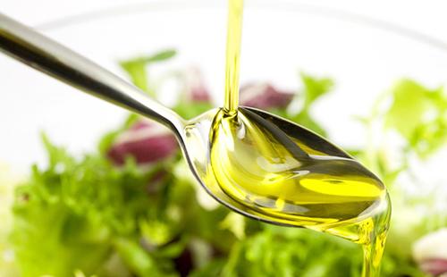 Золотая струйка масла льётся в ложку
