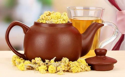 Керамический чайник полон жёлтых соцветий