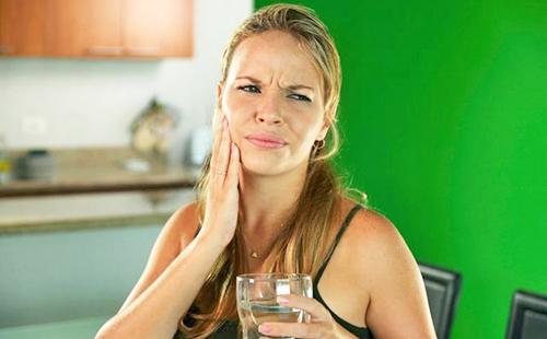 У женщины болит зуб, и она надеется на травяное полоскание
