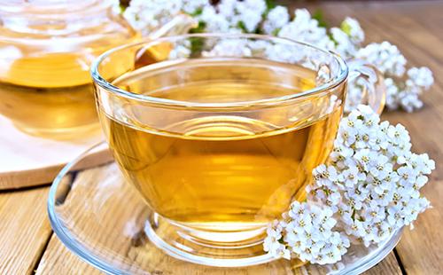 Чашка золотистого чаю и пенка нежных цветов