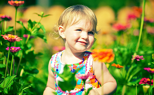 Чудесная девчушка стоит среди цветов