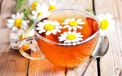 Чашка с цветочным янтарным чаем стоит на деревянном столе