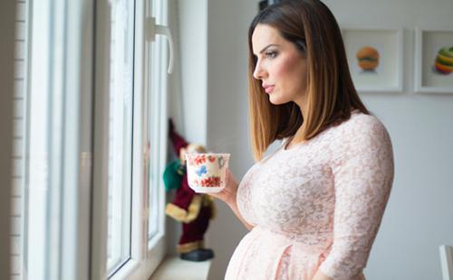 Женщина в интересном положении держит перед собой разрисованную чашку и смотрит в окно
