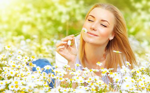 Девушка с улыбкой вдыхает аромат ромашек