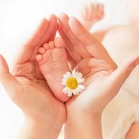 Мамины руки нежно держат крохотную младенческую пяточку