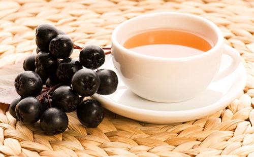 Настой в белой чашке и гроздь чёрных ягод