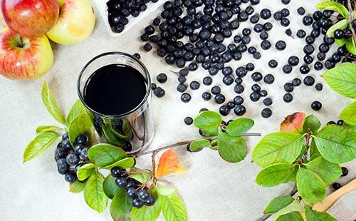 Стакан чернейшего напитка стоит среди рассыпанных ягод и яблок