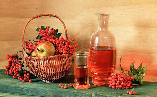 Плетёная корзина с ягодами и яблоками стоит рядом с большой бутылью настойки