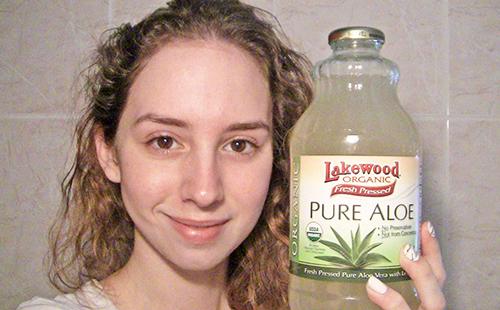 Кареглазая девушка показывает бутылку экологически чистого лосьона