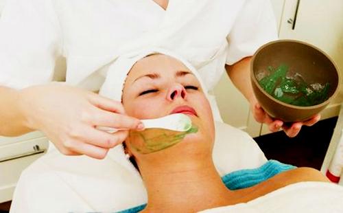 Косметолог наносит на щёки женщины смесь с алоэ