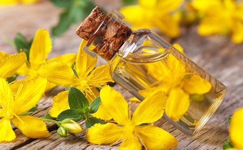 Натуральное масло в пузырьке среди жёлтых цветов