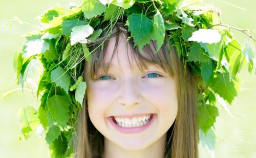 Смеющаяся девочка в венке из листьев
