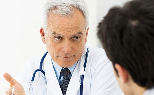 Опытный доктор что-то объясняет пациенту