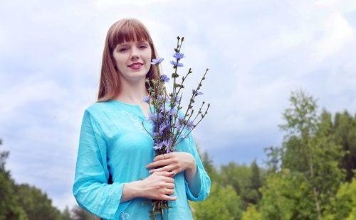 Девушка держит букет из цветов цикория