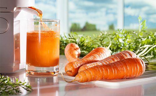 Морковный сок течет из соковыжималки