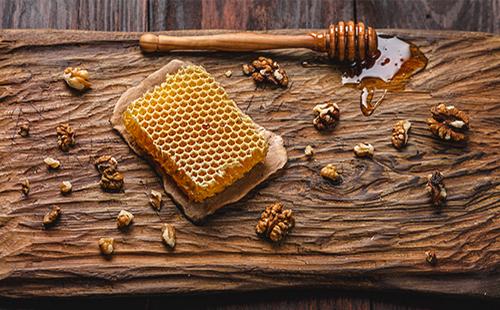 На деревянной доске соты с медом и грецкие орехи