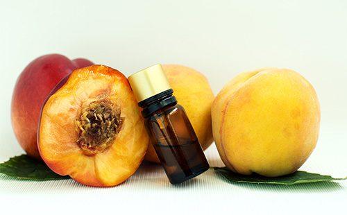 Персики и масло из их косточек в бутылке