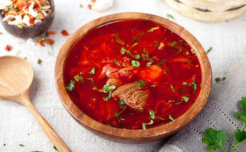 Красный борщ в деревянной тарелке