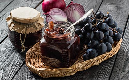 Варенье из темного винограда в банке и лук на столе