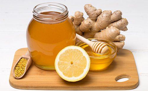 Половина лимона, мед в банке и имбирь на доске