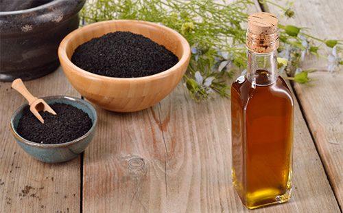 СЕмена черного тмина в пиале и масло в бутылочке
