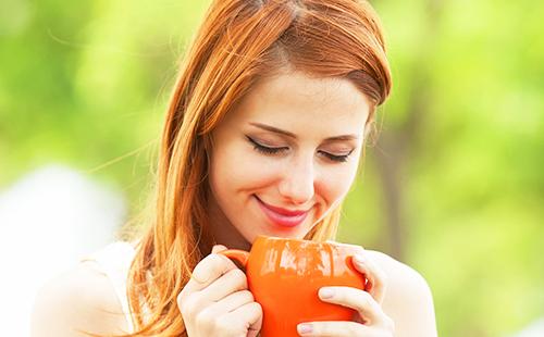 Рыжая девушка пьёт отвар из большой оранжевой чашки