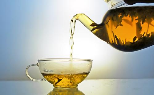 Золотистый травяной отвар льётся струйкой в чашку