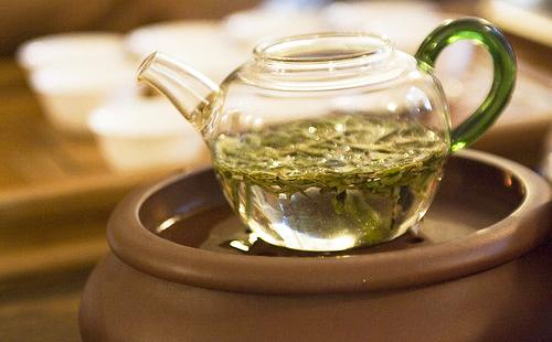 Травяной настой в прозрачном чайнике стоит на водяной бане