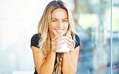 Весёлая блондинка пьёт травяной чай из белой кружки
