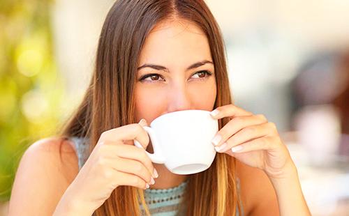 Кареглазая девушка с распущенными волосами пьёт чай из белой чашки