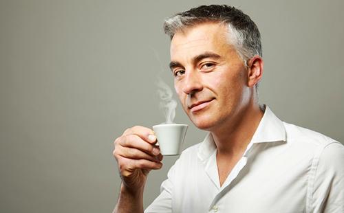 Седеющий мужчина с многозначительной улыбкой держит чашку