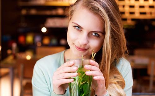 Девушка с лукавым взглядом пьёт мятный чай