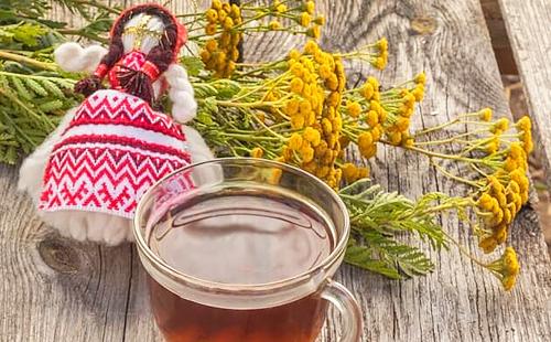 Цветы маточника рядом с чашкой с отваром и маленькой куклой, предназначенной ни для кого