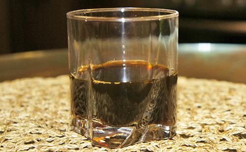 Тёмный травяной отвар в гранёном стакане
