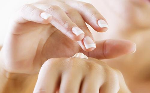 Красивые девичьи руки намазываются кремом