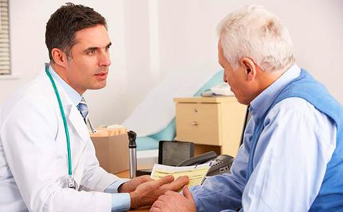 Пожилой пациент внимательно слушает врача приятной наружности