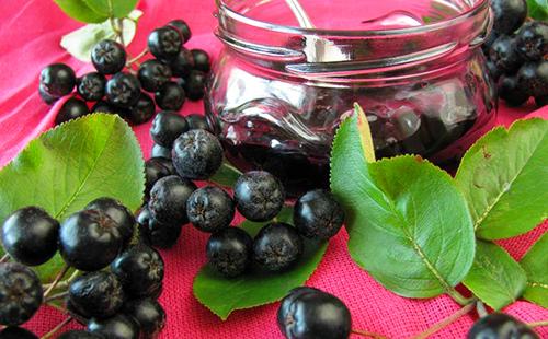 Рассыпанные ягоды, листья и стеклянная баночка с ложкой