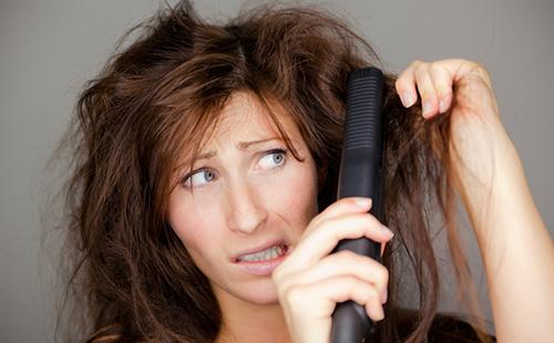 Женщина пытается расчесать плохие волосы