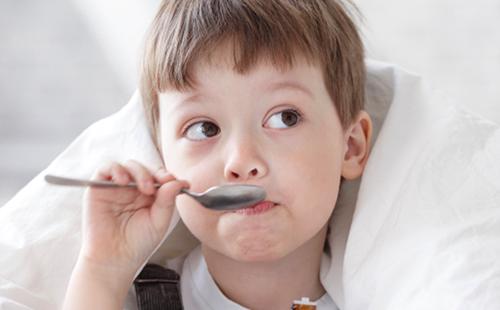 Мальчик пьёт сироп из ложки