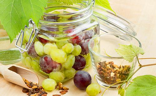 В стеклянной банке зеленый и красный виноград со специями